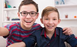 Two stylish smiling teens taking selfie. Two handsome teenage boys taking selfie while posing with smile to phone at home. Wearing glasses and braces. Friendship Stock Photography