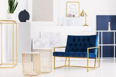 Two stylish tables next to petrol blue armchair in bright living room interior of modern apartment. Real photo royalty free stock photo