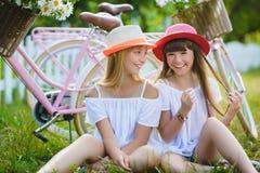 Two stylish teenage girlfriends on bicycle. Best friends enjoying day on bike.  royalty free stock photography