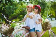 Two stylish teenage girlfriends on bicycle. Best friends enjoying day on bike.  royalty free stock photo