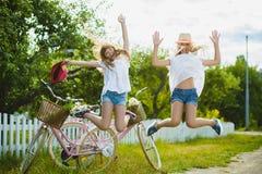 Two stylish teenage girlfriends on bicycle. Best friends enjoying day on bike.  stock image