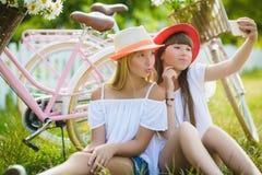 Two stylish teenage girlfriends on bicycle. Best friends enjoying day on bike.  royalty free stock image