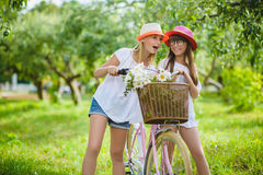 Two stylish teenage girlfriends on bicycle. Best friends enjoying day on bike.  royalty free stock images