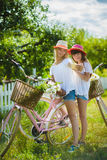 Two stylish teenage girlfriends on bicycle. Best friends enjoying day on bike.  royalty free stock photos