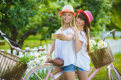 Two stylish teenage girlfriends on bicycle. Best friends enjoying day on bike.  stock photo