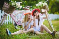 Two stylish teenage girlfriends on bicycle. Best friends enjoying day on bike.  stock photography