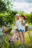 Two stylish teenage girlfriends on bicycle. Best friends enjoying day on bike.  stock photos