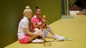 Two stylish tennis players relaxing in the sun. Two stylish young female tennis players relaxing in the sun against a club wall chatting as they wait to play stock footage