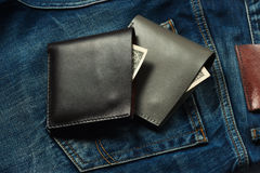 Two stylish wallet with money in a brown jeans pocket Stock Photos