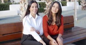 Two stylish woman sitting chatting outdoors stock video