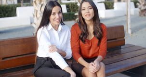 Two stylish woman sitting chatting outdoors Royalty Free Stock Photography