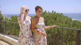 Two stylish woman walking on an outdoor patio. Two stylish young woman in summer attire walking arm in arm on an outdoor patio overlooking the coast and ocean stock video