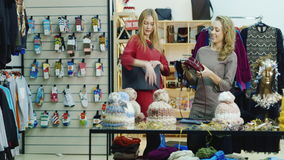 Two stylish women in beautiful dresses vybiirayut bags in a shop of women`s accessories and clothing stock footage