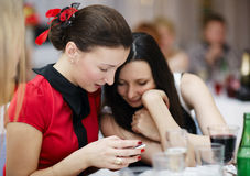 Two stylish women at an event reading sms Stock Photo