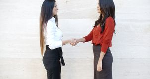 Two stylish women shaking hands outdoors. Two stylish women standing in profile shaking hands outdoors in front of a white wall  bilateral copyspace stock video