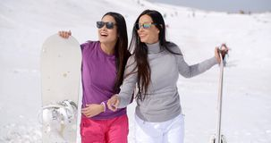 Two stylish women with their snowboards. Two stylish women wearing sunglasses standing in fresh white winter snow with their snowboards pointing at something in stock footage