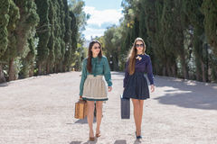Two stylish women walking with suitcases Royalty Free Stock Photo