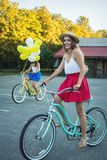 Two stylish young female friends on a bicycle in park. Best friends enjoying a day on bike Stock Image