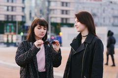 Two stylish young girlfriends wearing casual walk around the city and communicate. one girl holding sunglasses. Two stylish girlfriends wearing casual walk Stock Image