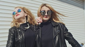 Two stylish young girls in leather jackets and sunglasses on a white background show a gesture. Finger down. Background stock video footage
