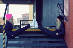 Two stylish young girls sitting on stairs Stock Photos