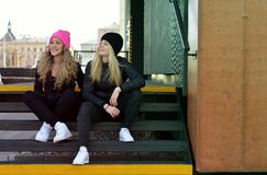 Two stylish young girls sitting on stairs Stock Images