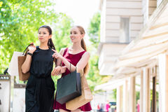 Two stylish young ladies out shopping. Standing in the street with their bags chatting and pointing Royalty Free Stock Image