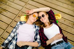 Two stylish young urban girls with longboards lie on the wooden flooring in the street. Friends have fun and spend time stock photo
