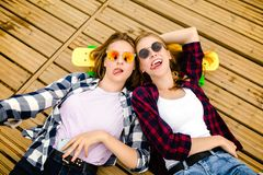 Two stylish young urban girls with longboards lie on the wooden flooring in the street. Friends have fun and spend time royalty free stock images