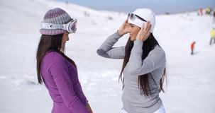 Two stylish young woman chatting at a ski resort. Standing in a snow landscape with tourists in the distance  close up upper body stock video