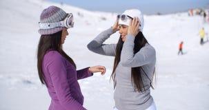 Two stylish young woman chatting at a ski resort Stock Image