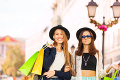 Two stylish young women walking with shopping bags Stock Photos