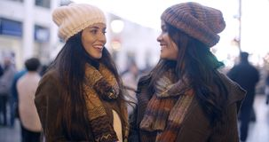 Two stylish young women in winter fashion. Standing outdoors in an urban street laughing and chatting  upper body pose stock video footage