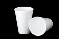 Two styrofoam cups on black. Two empty styrofoam cups on a black background. One up is upright and the second cup lays next to the first royalty free stock photos
