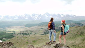 Two successful backpacker enjoy the beautiful landscape at mountain peak.  stock video