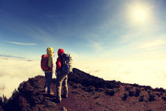 Two successful backpackers enjoy the beautiful landscape on sunrise mountian. Peak royalty free stock photo