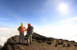 Two successful backpackers enjoy the beautiful landscape on sunrise mountian Stock Images