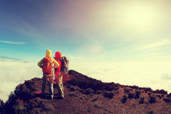 Two successful backpackers enjoy the beautiful landscape on sunrise mountian Royalty Free Stock Photo