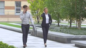 Two successful business colleagues walking on the street of an business center. slow motion. Two business colleagues in discussion, businesspeople walking on the stock video footage