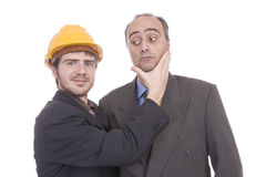 Two successful business man. One of them is architect with a yellow construction helmet Stock Photos