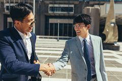 Two successful business men shaking hands royalty free stock photography