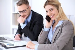 Two successful business partners working at meeting in office. Focus on blonde while talking by phone Royalty Free Stock Photo
