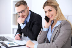 Two successful business partners working at meeting in office. Focus on blonde while talking by phone Royalty Free Stock Photography