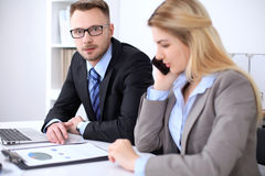 Two successful business partners working at meeting in office. Focus on blonde while talking by phone.  Royalty Free Stock Photo
