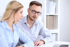 Two successful business partners working at meeting in office. Focus on man Royalty Free Stock Photos