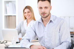 Two successful business partners working at meeting in office. Focus on man Royalty Free Stock Photo