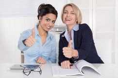 Two successful business women with thumbs up at office. Two happy smiling women with thumbs up at desk Stock Photos