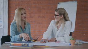 Two successful business women are working on a project. dispute between women 30-40 years old. ladies discussing a