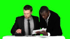 Two successful businessman sit down at the negotiating table in the office and working at his laptop. Green screen. Business work, two successful businessman stock video