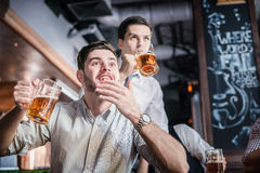 Two successful businessmen drink beer and rejoice and shout toge Royalty Free Stock Photos